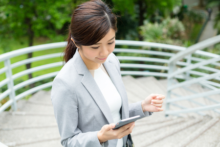 up stair: Asian Businesswoman read the message on cellphone and going up stair Stock Photo