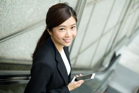 businesswoman standing: Businesswoman standing on escalator Stock Photo