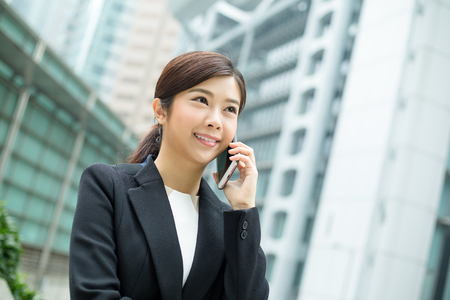 far away look: Young business woman talk to mobile phone Stock Photo