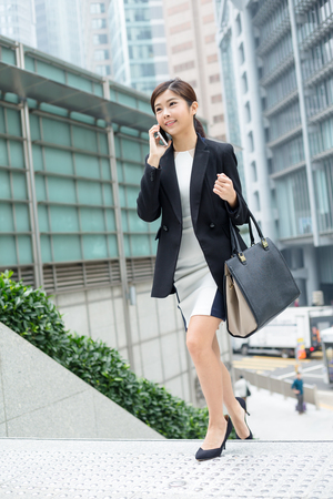up stair: Businesswoman walking up to stair and talk to mobile phone Stock Photo