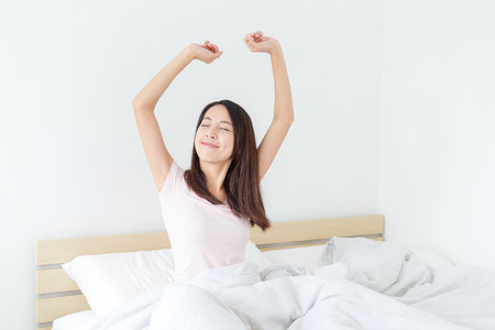 Woman wake up and stretch her arm