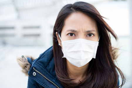 transmissible: Woman wearing face mask Stock Photo
