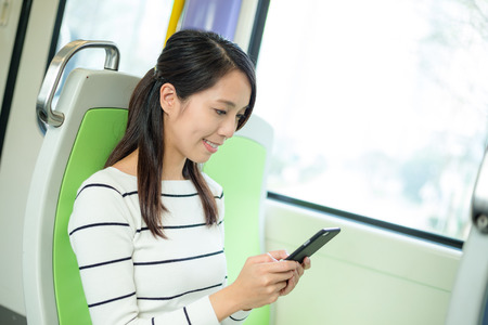 compartment: woman using cellphone inside train compartment