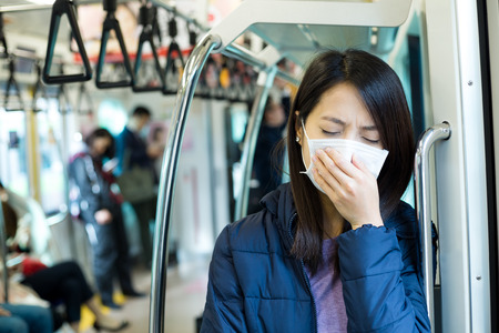 compartment: Passenger feeling unwell with face mask inside train compartment Stock Photo