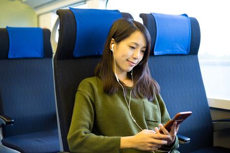 女性は列車コンパートメントに座って音楽を聴く 写真素材