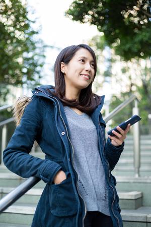 lejos: uso de la mujer del teléfono móvil y mirando a lo lejos