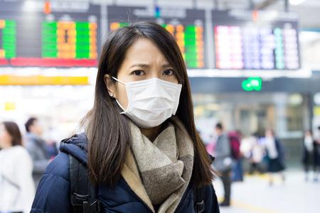 Woman wearing face mask at train station Banco de Imagens