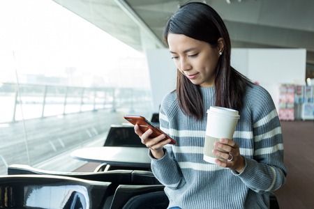 Woman use of mobile phone and hold with paper cup