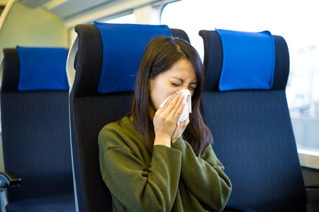 compartment: Woman sneezing inside train compartment