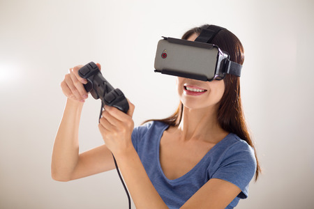 though: Asian Woman play video game though VR device Stock Photo