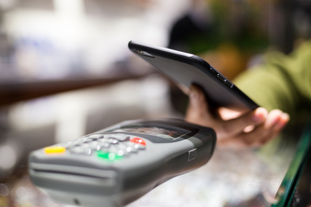 paying: Woman paying with NFC technology on cellphone Stock Photo