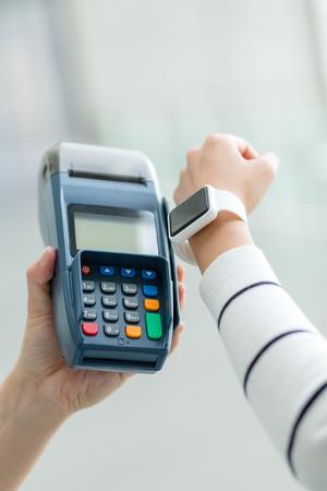 settle: Woman using smart watch to settle the bill