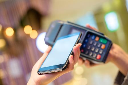 Vrouw met behulp van mobiele telefoon te betalen Stockfoto