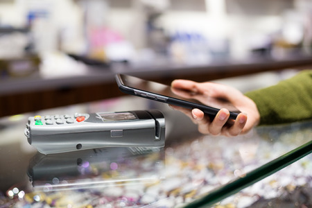 mobilephone: Female customer paying with mobilephone over electronic reader