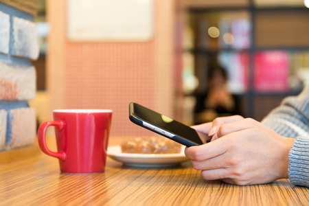 sending: Woman sending sms on mobile phone in cafe