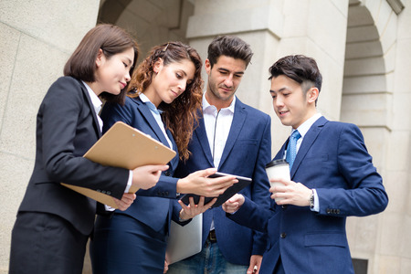 discuss: Group of business people discuss on tablet Stock Photo