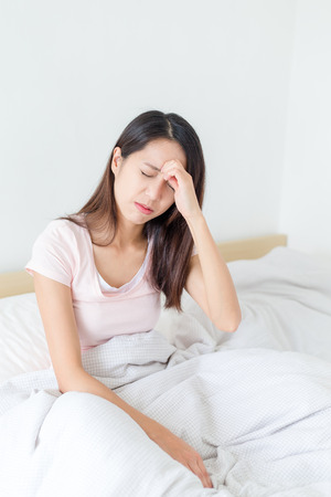 dizzy: Woman feeling dizzy and sitting on bed