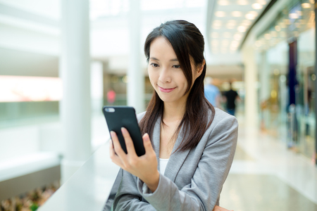 office use: Casual business woman looking at cellphone Stock Photo