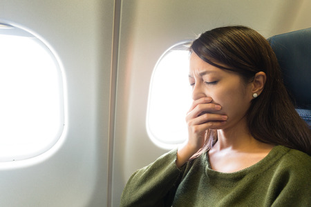 Woman feeling tried on aircraft