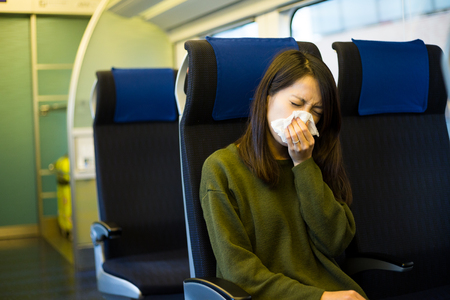 compartment: Woman sneeze inside train compartment Stock Photo