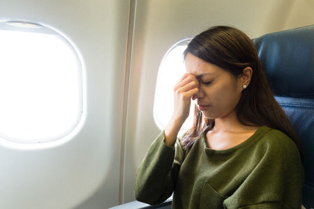flying woman: Fear of flying woman in plane airsick with stress headache