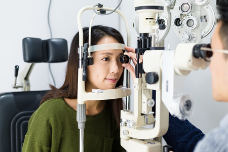 visual therapy: Woman checking vision with tonometer at optical clinic