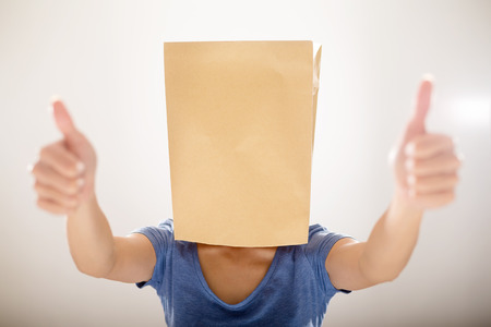 humiliated: Woman cover a paper bag and showing thumb up