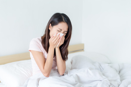 sniffles: Sick woman blowing lying on her bed at home Stock Photo