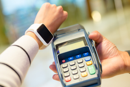 internet terminal: Woman using wearable smartwatch for paying on pos machine