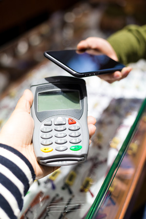wireless terminals: Woman pay with mobile phone by NFC