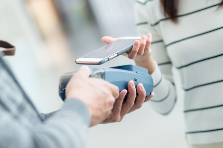 paying: Female paying with NFC technology on smart phone