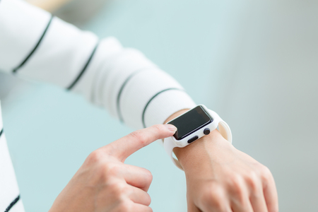 girl with a wristwatch: Woma use of smart watch Stock Photo