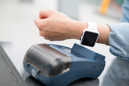 nfc: Woman paying the bill by smart watch by NFC technology Stock Photo