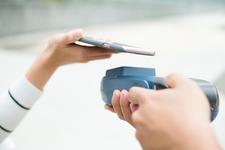 paying: Woman paying with NFC technology
