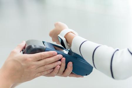 wireless terminals: Female customer paying through smart watch
