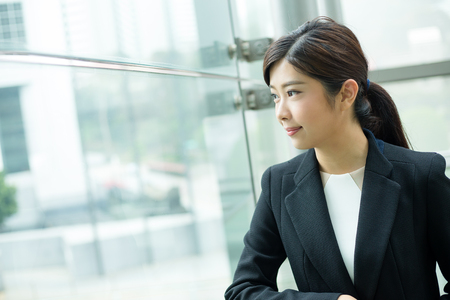 looking out: Businesswoman looking out of window Stock Photo