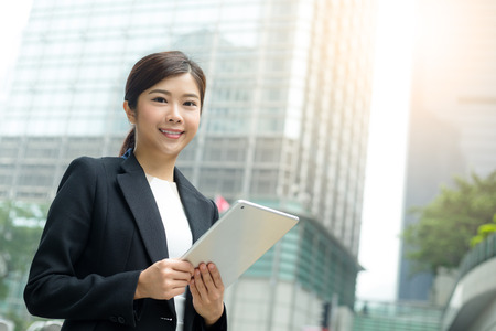 topicality: Business woman using tablet pc in front of office building Stock Photo