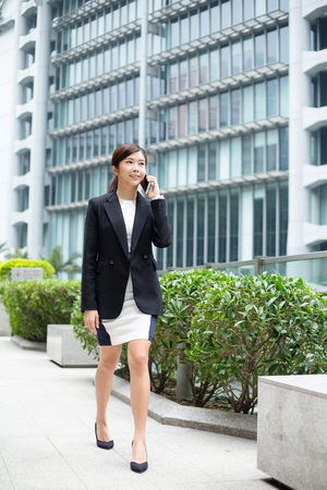 Businesswoman talk to cellphone and walking at street