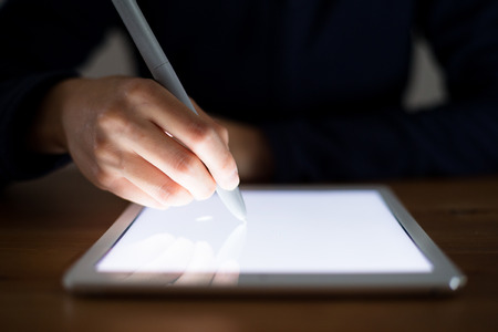 delineation: Woman using pen drawing on tablet pc