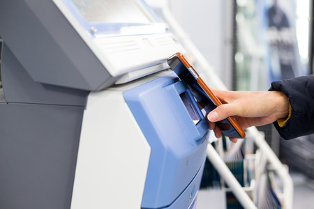 ticketing: Woman using smartphone for scanning on ticketing machine by NFC