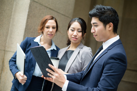 chinese american ethnicity: Business people discuss on tablet Stock Photo