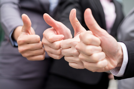 Business partners keeping thumbs up Stock Photo