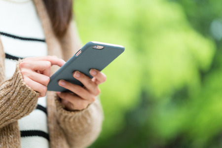 body parts cell phone: Woman use of mobile phone over green background