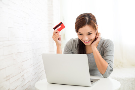 Woman enjoy online shopping paying by credit card Imagens