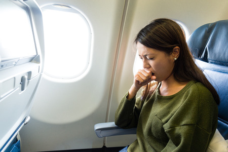 Woman feeling sick inside air plane Stock Photo