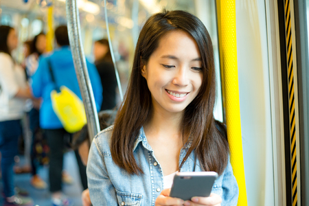 compartment: Woman using cellphone in train compartment