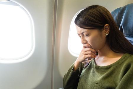 Vliegangst vrouw in vliegtuig luchtziek