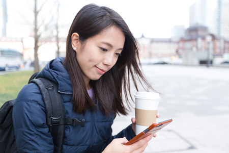 Woman use of cellphone and drink of coffee