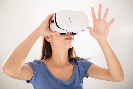 though: Woman watching though VR device and hand touch on something