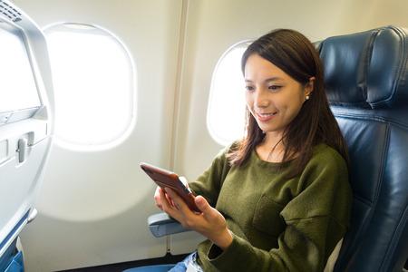 gebruik vrouw van de slimme telefoon in vliegtuig